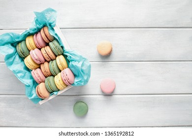 Assortment of fresh french macarons packaged in a pretty white wooden box with blue tissue on a white rustic table. Image shot from above with room for text.