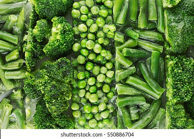 Assortment of fresh frozen green peas, french bean, broccoli with hoarfrost closeup as background. Healthy vitamin food.