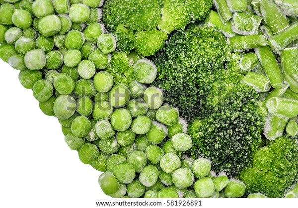 Assortment of fresh frozen vegetables with rime frost, peas, beans, broccoli closeup. Healthy food background. Top view.