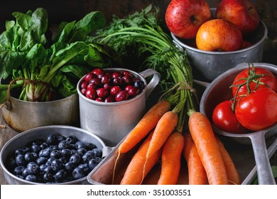 Assortment of fresh fruits, vegetables and berries. Bunch of carrots, spinach, tomatoes and red apples, blueberries and cranberries in vintage aluminum utensil over old wooden table.