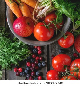 Assortment of fresh fruits, vegetables and berries. Bunch of carrots, spinach, tomatoes and red apples in vintage metal bowl, blueberries and cranberries over old wooden table. Top view. Square image
