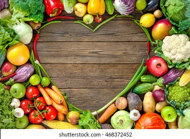 Assortment of  fresh fruits and vegetables in heart shape on wooden background