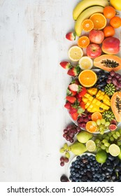 Assortment of fresh fruits and vegetables in rainbow colours background on the off white table vertical, top view, selective focus