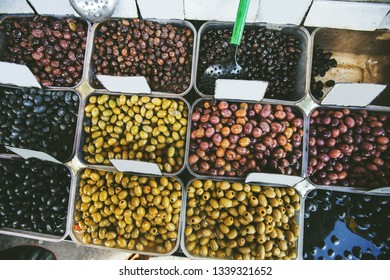 Assortment of fresh healthy green and black olives for sale at farmers food market