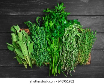 Assortment of fresh herbs for meat and fish, tarragon, parsley, rosemary, thyme, sage. Black wood background. Top view.