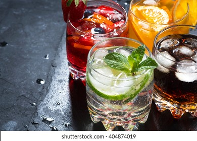 assortment of fresh iced fruit drinks on a black background, closeup