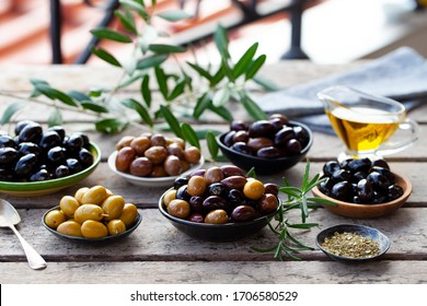 Assortment of fresh olives on a plate with olive tree brunches. Wooden background.