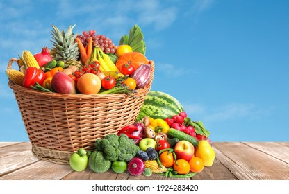 Assortment of fresh organic fruits and vegetables on wooden table outdoors