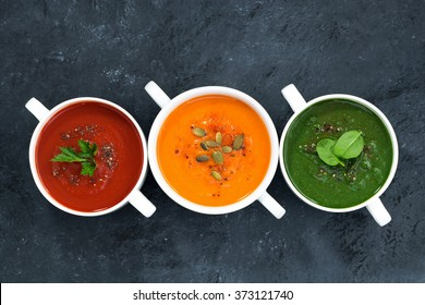 assortment of fresh vegetable soup on a dark background, top view