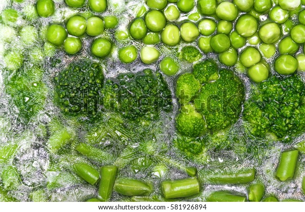 Assortment of fresh vegetables, frozen in ice, green peas, beans, broccoli closeup. Healthy food background.