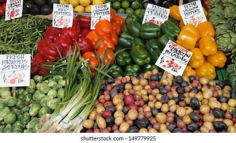 Assortment of fresh vegetables on display in open air farmers market.