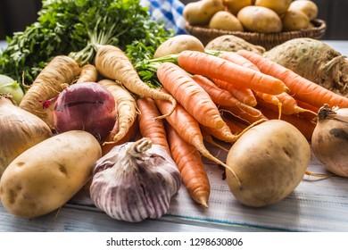 Assortment of fresh vegetables on wooden table. Carrot parsnip garlic celery onion and kohlrabi.