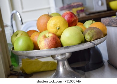 Assortment of fresh whole fruits piled on a metal stand in the kitchen