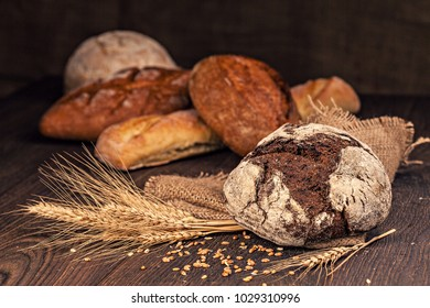Assortment of freshly baked breads with ears of wheat  in rustic setting. Shallow depth of field.