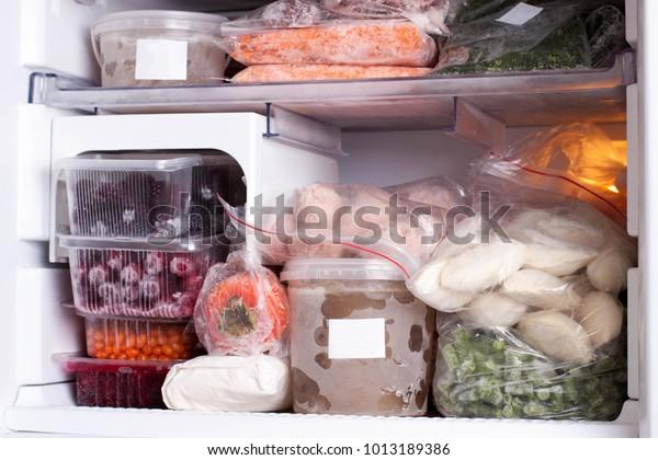Assortment of frozen vegetables, meat and dumplings in home fridge