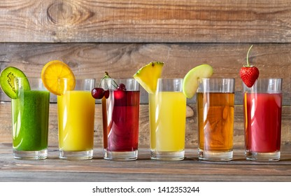 Assortment of fruit juices on the wooden background