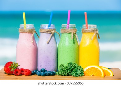 Assortment of fruit smoothies against a beach background