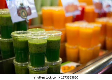 Assortment of fruit smoothies served in cups on street market