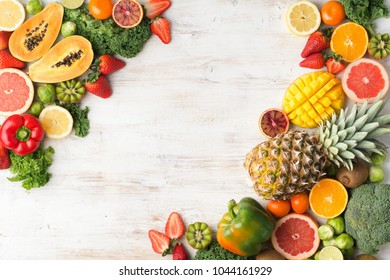 Assortment of fruits and vegetables rich in vitamin C, copy space, oranges mango grapefruit kiwi kale pepper pineapple lemon sprouts papaya broccoli, on wooden white table, top view, selective focus