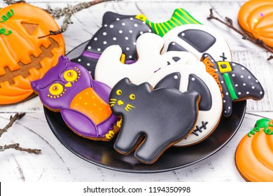 Assortment of gingerbread cookies - owl, witch, pumpkin, hat, ghost and black cat on black plate. Trick or treat, kids party or candy bar concept. Copy space