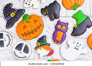 Assortment of gingerbread cookies - owl, witch, pumpkin, hat, ghost and black cat on white halloween background. Trick or treat, kids party or candy bar concept. Copy space