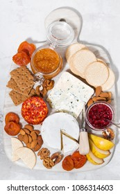 assortment of gourmet cheeses and snacks on board, vertical