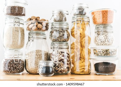 Assortment of grain products and pasta in glass storage containers on wooden table. Healthy cooking, clean eating, zero waste concept. Balanced dieting food.