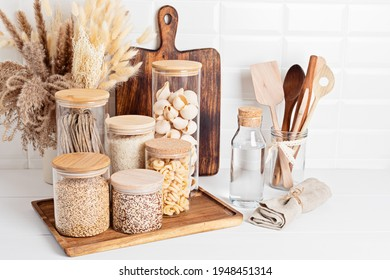 Assortment of grains, cereals and pasta in glass jars and kitchen utensils on wooden table. Healthy balanced food, sustainable lifestyle, zero waste storage, eco friendly idea - Shutterstock ID 1948451314