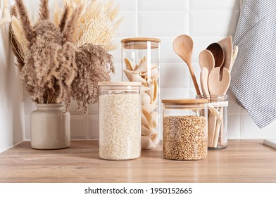 Assortment of grains, cereals and pasta in glass jars and kitchen utensils on wooden table - Shutterstock ID 1950152665