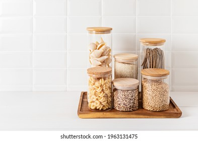 Assortment of grains, cereals and pasta in glass jars and dry herbs on wooden table. Healthy balanced food ingredients, sustainable lifestyle, zero waste storage idea, eco friendly concept.