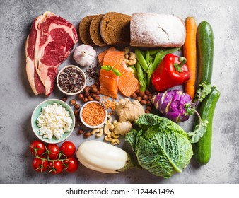 Assortment of healthy balanced food composition: meat, fish, vegetables, bread, cereals, beans, stone background. Raw ingredients for cooking healthy meal, good for diet, clean eating concept