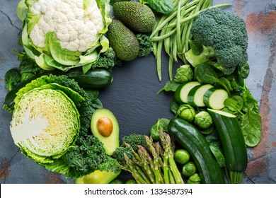 Assortment of healthy organic green vegetables for balanced eating. Vegan, vegetarian, whole food, plant based, clean eating concept. Top view flat lay copy space background