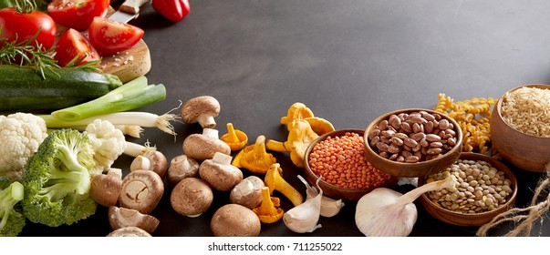 An assortment of healthy, organic harvest produce, legumes and vegetables on a dark grey background with copy space in a panoramic orientation.