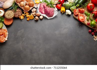 An assortment of healthy, organic, paleo harvest produce, legumes, meats and vegetables on a dark rustic grey background with copy space.