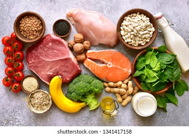 Assortment of healthy protein sources and body building food : meat, fish, fruits, vegetables, legumes, nuts, cereals and dairy products on a light  slate, stone or concrete background.Top view with c