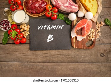 Assortment of high vitamin B sources on wooden background: milk, liver, olive oil, tomatoes, peanuts, beef, spinach, salmon, keshew, cheese, eggs. Top view.