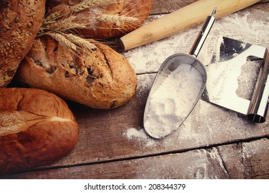 Assortment of homemade breads on wood with cooking utensils