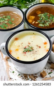 assortment of hot soups in mugs on wooden background, closeup vertical