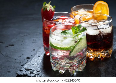 assortment of iced fruit drinks on a dark background, horizontal