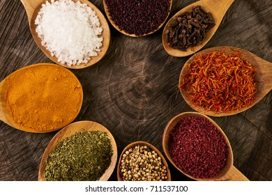Assortment of indian spices and herbs in wooden spoon on wooden stump. Top view