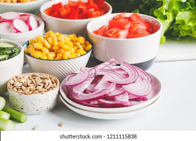 Assortment ingredients for healthy vegetarian salad in different portion bowls on a table. The concept of fitness and vegan food.