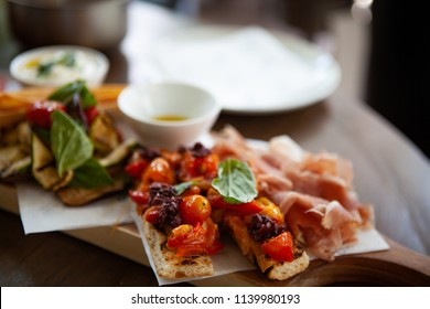 Assortment of Italian antipasto. Delicious and colorful Bruschetta topped with grilled cherry tomatoes and Prosciutto di Parma or Parma ham and grilled vegetable on a wooden board. Natural light.