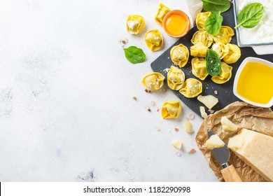 Assortment of italian food and ingredients, handmade tortellini with green spinach and ricotta cheese on a cutting board on a kitchen table. Top view flat lay copy space background