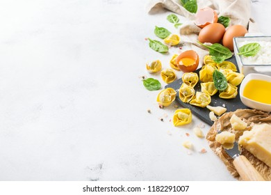 Assortment of italian food and ingredients, handmade tortellini with green spinach and ricotta cheese on a cutting board on a kitchen table. Copy space background