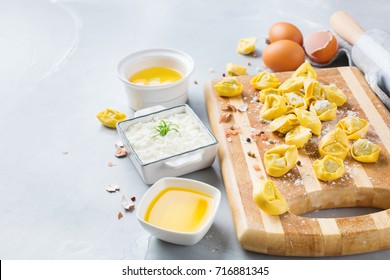 Assortment of italian food and ingredients, handmade tortellini with ricotta on a table. Copy space background