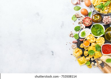 Assortment of italian food and ingredients, ravioli with ricotta and spinach pasta tortellini pesto tomato sauce olive oil parmesan cheese. Top view flat lay copy space background