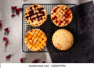 Assortment of Jam or marmalade filled crostata italian pies or tarts and apple pie on stone table, top view.