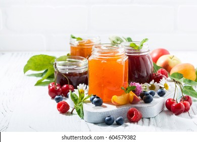 assortment of jams, seasonal fresh berries and fruits on white background, horizontal