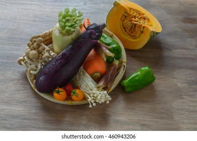 The assortment of Japanese vegetables in a bamboo basket on wooden background.