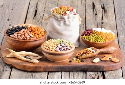 Assortment of legumes (Mung bean, Soya bean, Red kidney bean, Navy bean, Peanut) on wooden background.